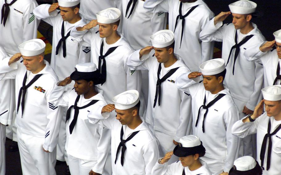 Sailors render honors during a burial at sea ceremony aboard USS John C. Stennis (CVN 74).  Committing to the sea cremated remains of honorably discharged military personnel is performed aboard U.S. Navy ships at the request of the deceased's family.