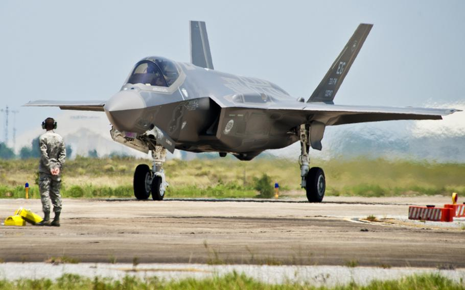 A 33rd Fighter Wing maintainer watches as the first F-35 Lightning II joint strike fighter taxis in to its new home at Eglin Air Force Base, Fla., July 14, 2011.