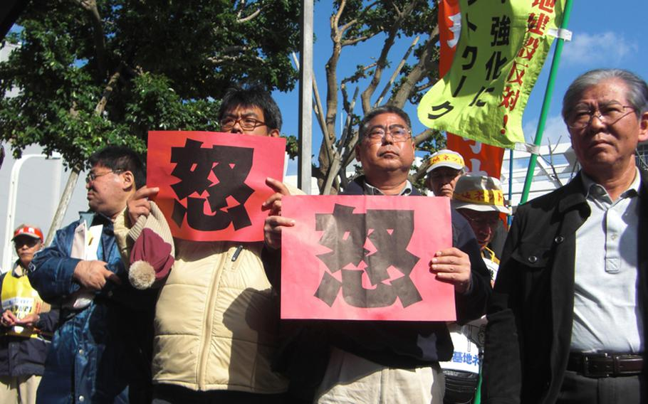 Holding cards that read 'wrath' in Chinese, protesters assemble for a second day on Dec. 28, 2011, at Okinawa prefectural office in an attempt to block a controversial environmental assessment report from being submitted to Okinawa government.
