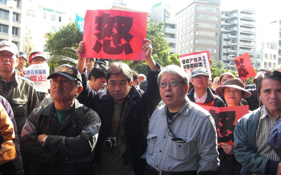 Protesters express their outrage by hoisting red cards with a Chinese character meaning 'wrath' at the prefectural government office in Okinawa on Dec. 28, 2011.