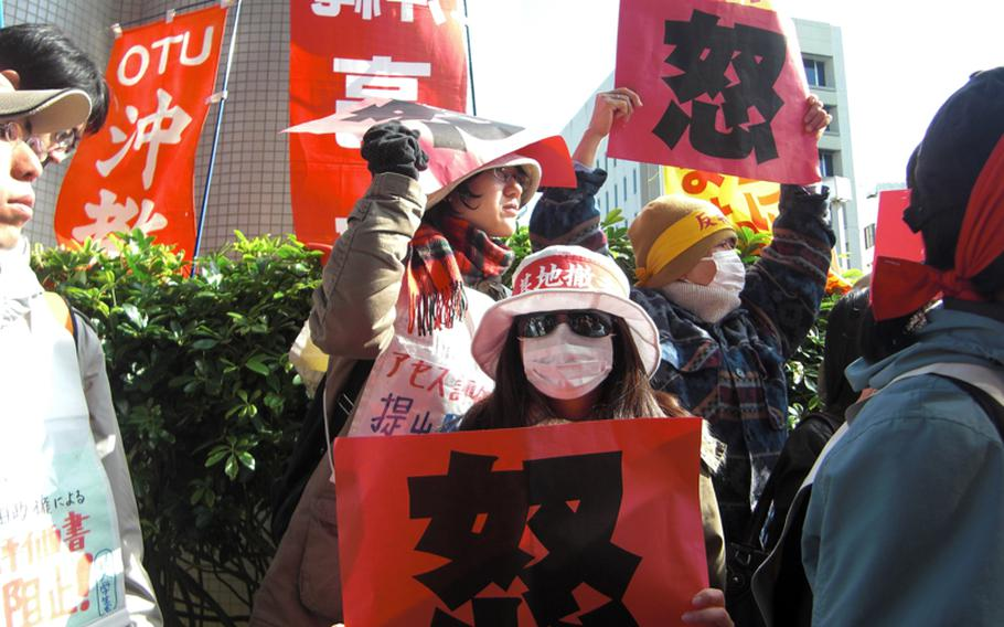 Protesters wave red cards that read 'wrath' in Chinese after discovering that an environmental assessment report for a new Marine Corps runway planned to be built on Camp Schwab had been delivered to the Okinawa prefectural government office on Dec. 28, 2011, before office hours.