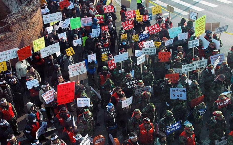 Protesters gather outside U.S. Army Garrison - Yongsan in December 2011 in response to the hiring of a new security firm at bases in South Korea. That security company, British-based G4S, is now being phased out immediately, with a new security firm set to take over security by the end of October.
