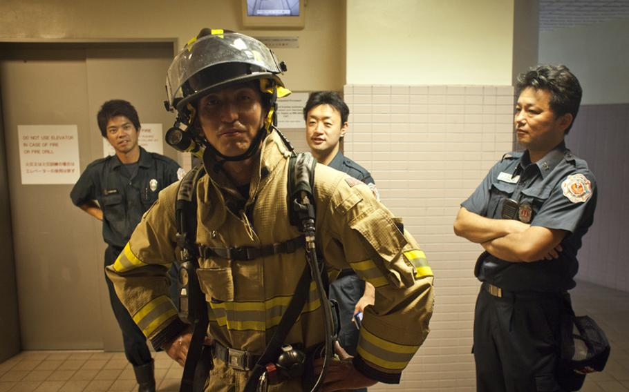 A firefighter from Naval Air Facility Atsugi, Japan poses after climbing 110 flights of stairs during a memorial stair climb at an on-base housing tower to honor the first responders of the Sept. 11, 2001, terrorist attack who lost their lives when the towers collapsed.