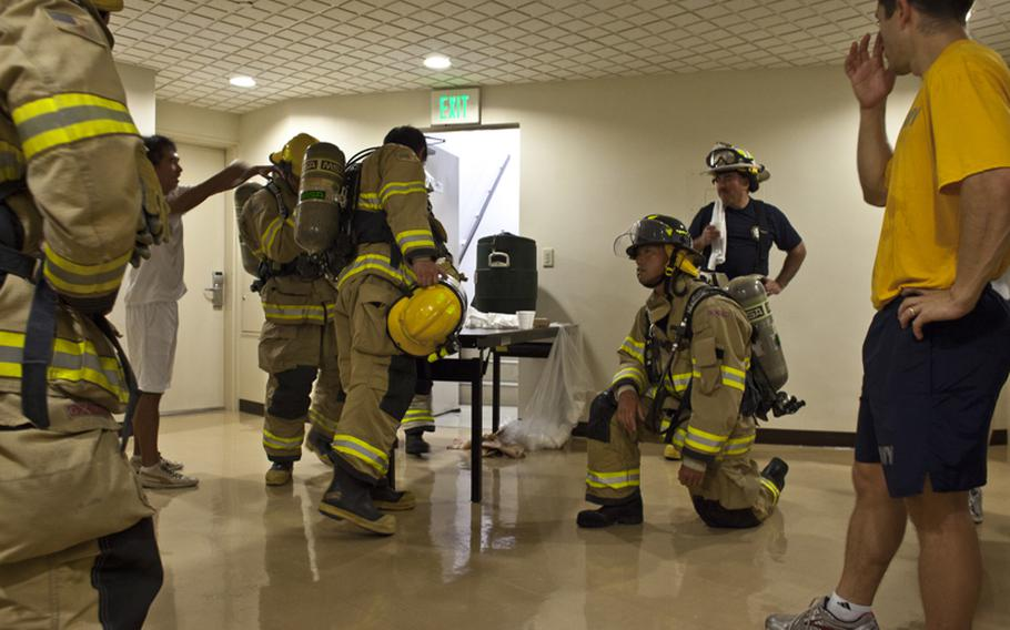 Firefighters from Naval Air Facility Atsugi, Japan, rest at the top floor of an on base housing tower during a memorial stair climb on Sept. 11, 2012. To honor the first responders of the Sept. 11 terrorist attack, more than 40 firefighters, medical personnel and security forces climbed 110 flights of stairs, the same number as the towers that fell on Sept. 11, 2001. The event commemorated the sacrifice of the emergency workers who died when the towers fell.
