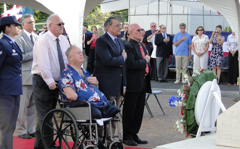 Former Sen. Max Cleland, a Vietnam veteran, in wheelchair, and Defense Secretary Leon Panetta, to his left, join others in observing the nation's veterans during a Veterans Day ceremony Nov. 11, 2012, at the National Memorial Cemetery of the Pacific in Hawaii. The crowd is facing a wreath Panetta laid in honor of Veterans Day.