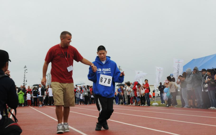 Marine Sgt. Eric Thurau from Marine Corps Air Station Futenma assists Kota Yane of Okinawa City in the 30-meter Dash during the 13th Kadena Special Olympics Saturday. The inter-community event began in 2000 with about 400 athletes. Twelve years later, participants grew more than double. On Saturday's event, about 3,000 servicemembers, civilians, their families and Japanese volunteers gather the air base to support the goodwill event.