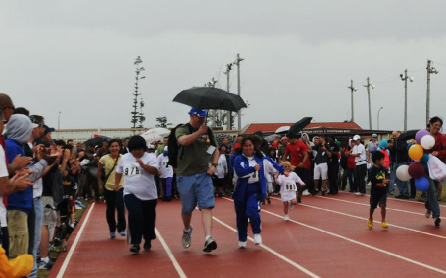 Special-needs athletes compete in 30-meter Dash Saturday during the Kadena Special Olympics games held at Kadena Air Base.  About 900 athletes from both Okinawa and U.S. military communities participate in the annual inter-community sports event. Also joining in the event are nearly 3,000 U.S. servicemembers, civilians, their families and Japanese volunteers, including cheer girls and band members from Kadena High School.