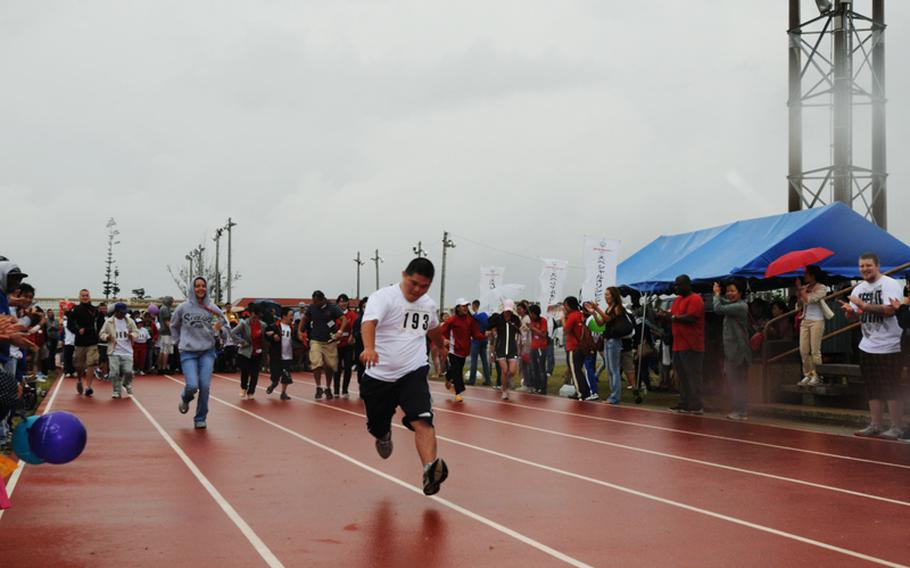 Tai Toguchi from Haebaru Town outruns his volunteer escort, Airman 1st Class Audrey McCleskey, in the 30-meter Dash during the 13th Kadena Special Olympics held at Kadena Air Base.