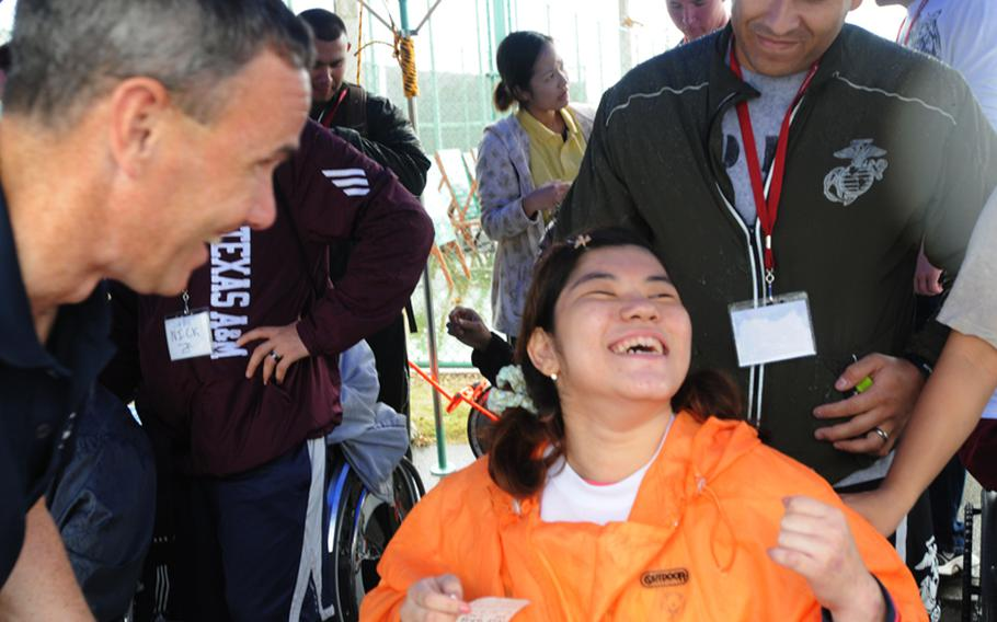 Nanami Tamayose smiles in relief after reading an English message she prepared to Capt. Richard Weathers, commanding officer of the Fleet Activities Okinawa.  For Tamayose, the annual Kadena Special Olympics is something she is looking forward to every year.  She participates in wheelchair softball throw Saturday.  About 900 special-needs athletes compete in the various games, while nearly 3,000 American and Japanese volunteers support the special event at Kadena Air Base Saturday.