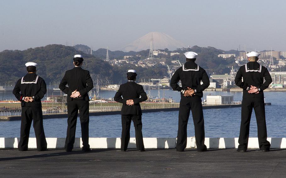 Sailors aboard the aircraft carrier USS George Washington face Mount Fuji in Yokosuka, Japan on Nov. 20, 2012.