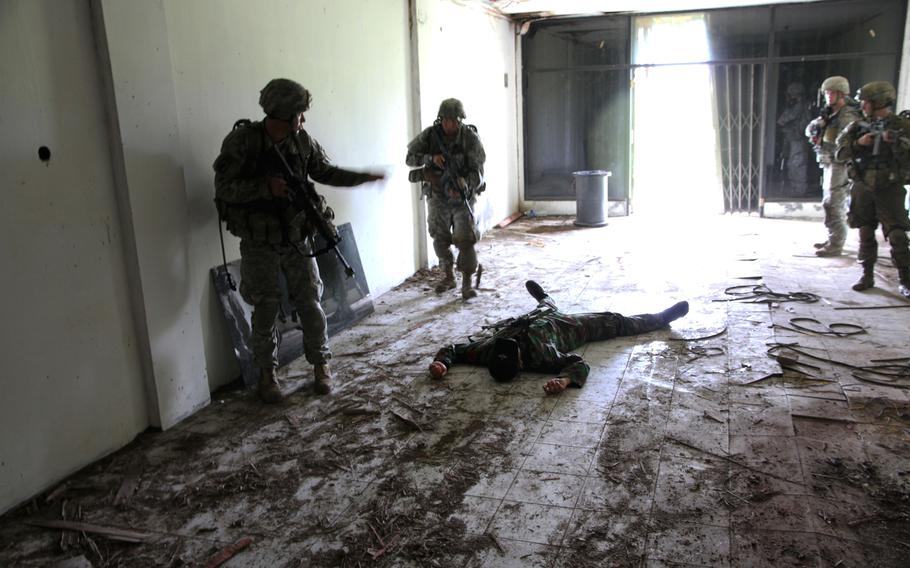 """Soldiers examine a """"dead"""" enemy as they clear a building during a mock UN peacekeeping scenario as part of Garuda Shield in Indonesia."""
