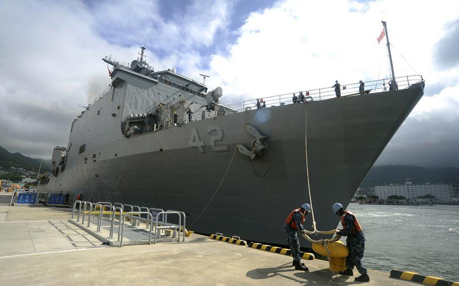 Sailors release a mooring line as the amphibious dock landing ship USS Germantown departs Sasebo, Japan, for a patrol in June 2011.