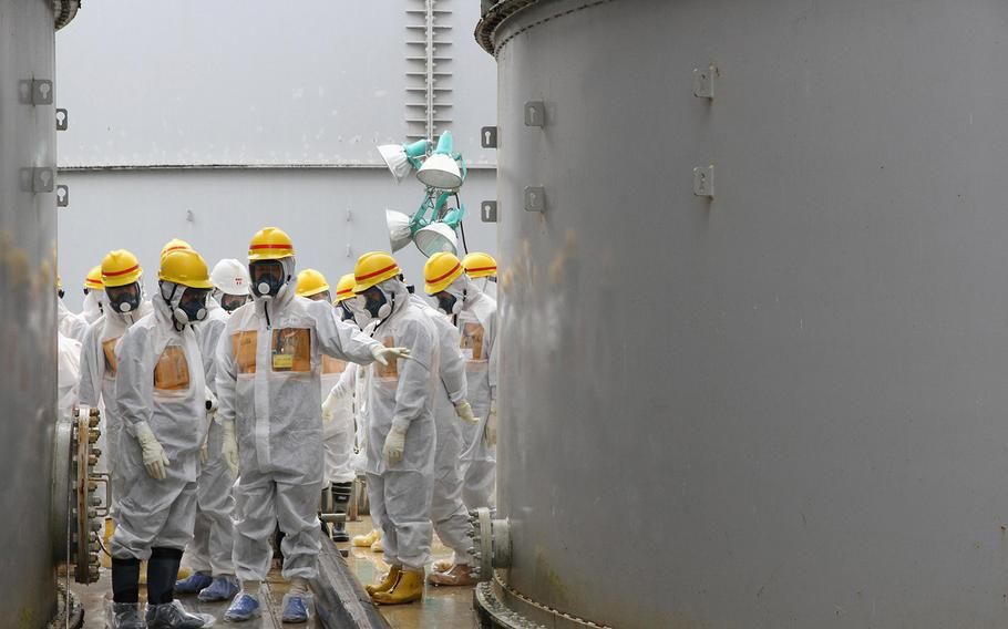 Nuclear Regulation Authority commissioners inspect storage tanks used to contain radioactive water at the Fukushima Dai-ichi nuclear power plant, operated by Tokyo Electric Power Co. in Fukushima prefecture, northern Japan, on Friday, Aug. 23, 2013.