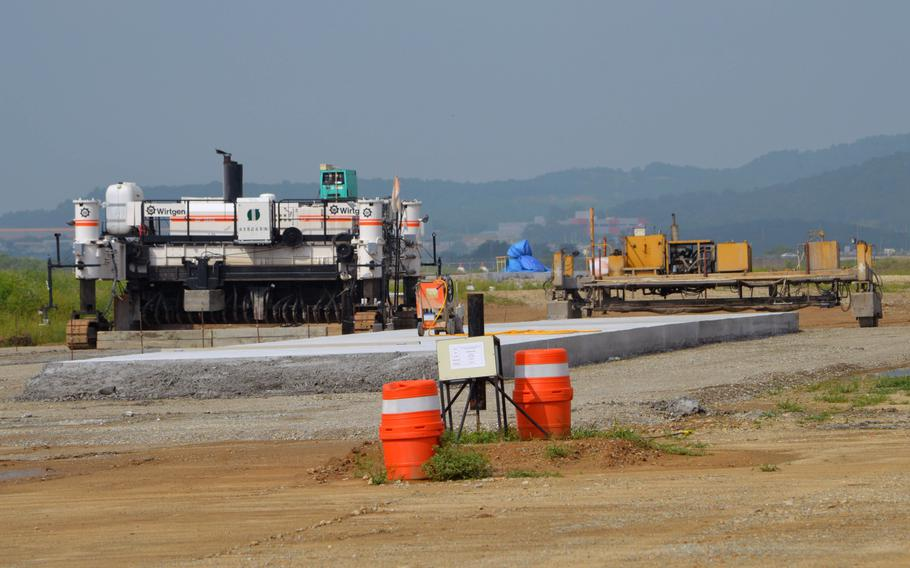 A portion of the concrete for the new runway sits partially finished at Osan Air Base, South Korea, Aug. 30, 2013. Construction equipment lies ready for use to continue construction of the second runway.