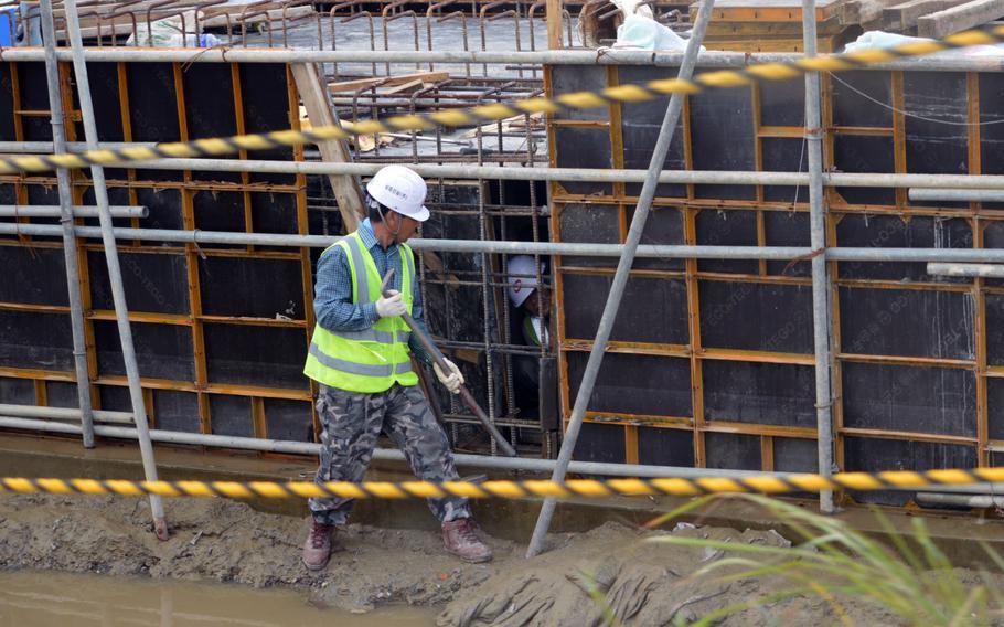 A construction crew works on runway construction at Osan Air Base, South Korea, Aug. 30, 2013.
