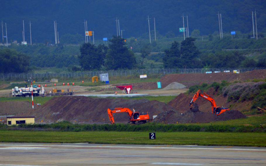 Construction crews dig and remove soil at a construction site at Osan Air Base, South Korea, Aug. 30, 2013. The construction will allow for a second parallel runway.
