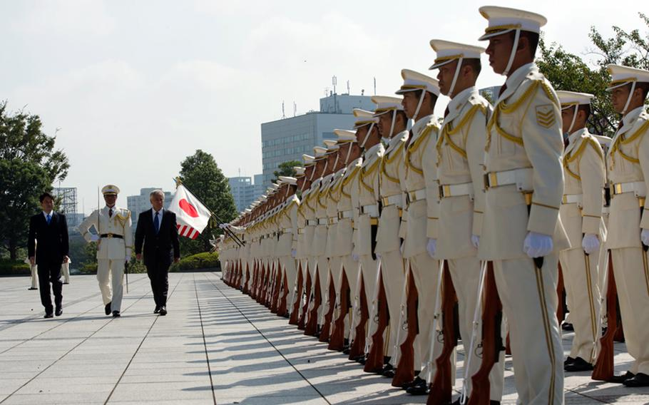 Japanese Defense Minister Itsunori Onodera escorts U.S. Defense Secretary Chuck Hagel, third from left, during a pass-in-review ceremony in Tokyo on Oct. 3, 2013. The two counterparts later met to discuss issues of mutual importance.