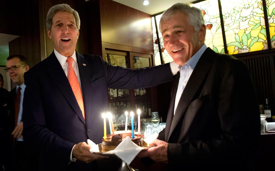 U.S. Secretary of State John F. Kerry, left, surprises U.S. Defense Secretary Chuck Hagel with a birthday cake after meetings with defense and foreign affairs counterparts in Tokyo on Oct. 3, 2013. Hagel's birthday is Oct. 4.