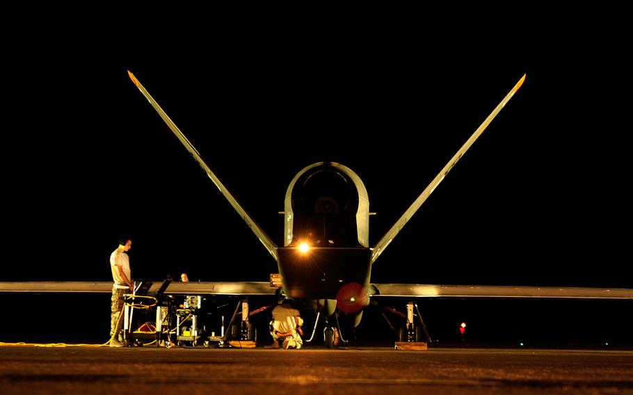 An Air Force technician works on preflight checks for a Global Hawk drone at an undisclosed base in Southwest Asia, Nov. 23, 2010.