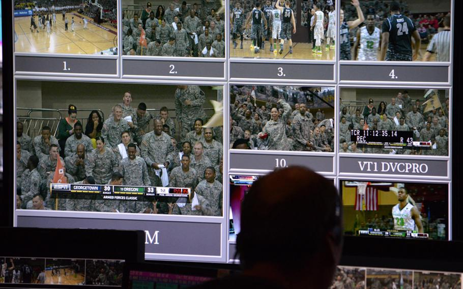 An ESPN production crewmember watchs a large monitor during the NCAA season-opening 2013 Armed Forces Classic at Camp Humphreys, South Korea, on Saturday, Nov. 9, 2013.