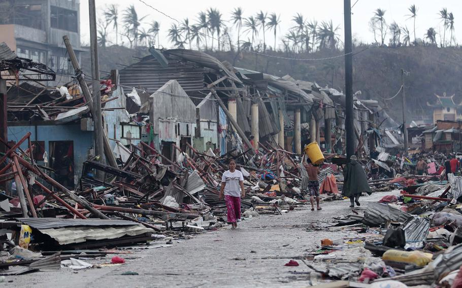 Residents walk past damaged structures caused by typhoon Haiyan,  in Tacloban city, Leyte province central Philippines on Sunday, Nov. 10, 2013. Haiyan, one of the most powerful typhoons ever recorded, slammed into central Philippine provinces Friday leaving a wide swath of destruction and scores of people dead.