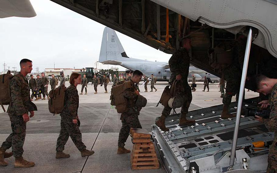 Marines board a KC-130J Hercules aircraft Sunday, Nov. 10, 2013, at Marine Corps Air Station Futenma, Okinawa, Japan, moments before departing for a humanitarian assistance and disaster relief mission to the Philippines.