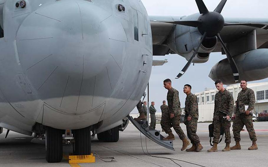 Marines board a KC-130J Hercules aircraft Sunday, Nov. 11, 2013, at Marine Corps Air Station Futenma, Okinawa, Japan, to depart for humanitarian assistance and disaster relief operations in the Philippines after Typhoon Haiyan.