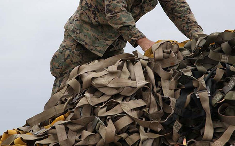 Chief Warrant Officer Allen T. Leiper uses cargo nets to secure palletized equipment Nov. 11 at Marine Corps Air Station Futenma, Okinawa, Japan. The equipment was later loaded onto a KC-130J Hercules aircraft to be used during humanitarian assistance and disaster relief operations in the Philippines in the aftermath of Typhoon Haiyan.