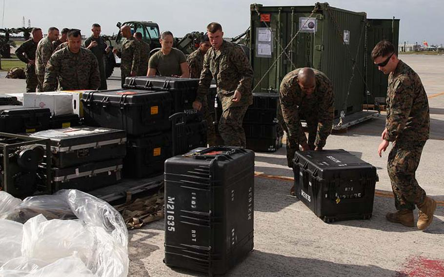 Marines preparing to depart for the Philippines ahead of Haiyan relief efforts stack their gear on a pallet Sunday, Nov. 10, 2013, at Marine Corps Air Station Futenma, Okinawa, Japan.