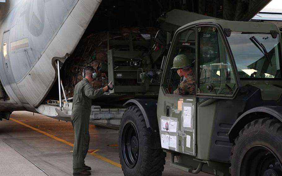 Gunnery Sgt. Joseph A. Zook, left, guides Lance Cpl. Bryce R. Sanglay while he loads a KC-130J Hercules aircraft Sunday, Nov. 10, 2013, at Marine Corps Air Station Futenma, Okinawa, Japan, during preparation for a humanitarian assistance and disaster relief mission to the Philippines after Typhoon Haiyan.