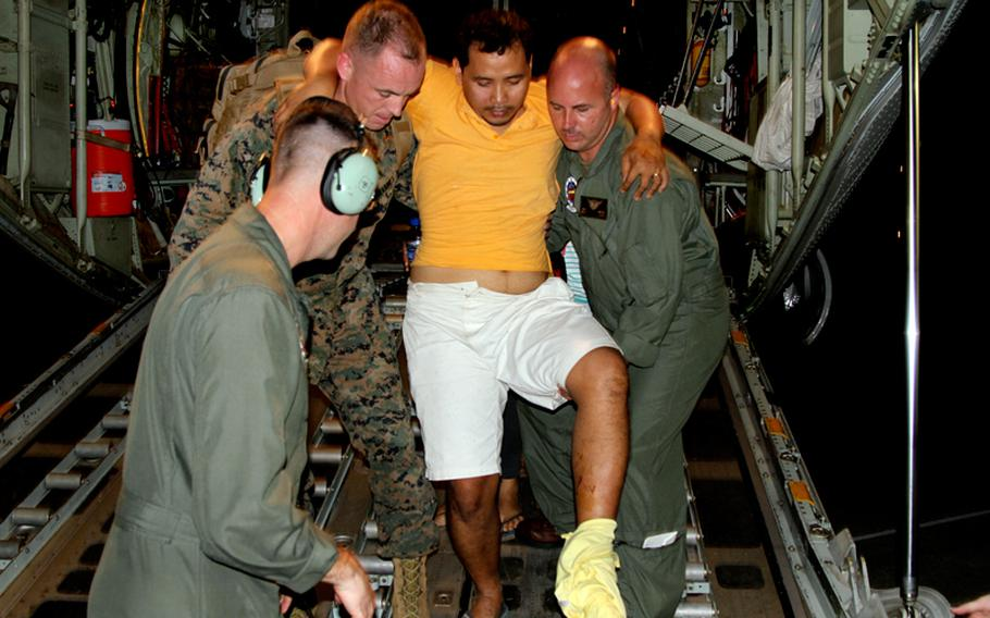 U.S. Marines carry an injured Filipino man off the back of a KC-130J Super Hercules at Villamor Air Base, Manila, the Philippines, on Monday, Nov. 11, 2013. Defense Secretary Chuck Hagel directed Marines to provide humanitarian relief after Typhoon Haiyan devastated parts of the country.