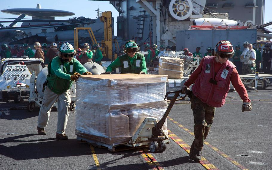 Sailors aboard the USS George Washington move a pallet of drinking water across the aircraft carrier's flight deck, as the George Washington Strike Group supports the 3rd Marine Expeditionary Brigade's relief efforts in the Philippines devastated by Super Typhoon Haiyan.