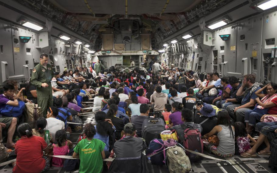 Displaced residents from Typhoon Haiyan prepare for takeoff inside a C-17 Globemaster from Tacloban Airport to Manila, Nov. 15, 2013. Evacuation and supply delivery are two of the ways U.S. military is working to assist Operation Damayan.
