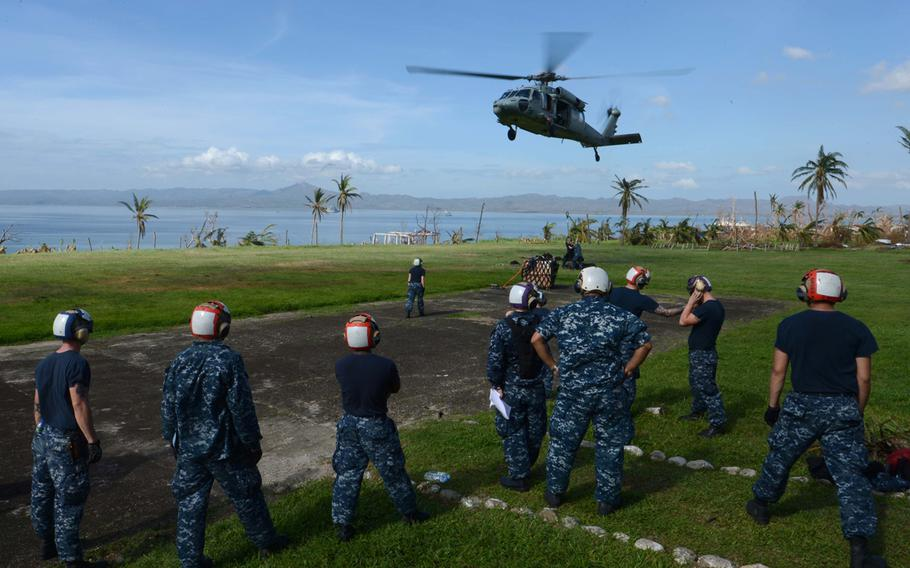 US troops wait for a Seahawk helicopter from the USS Mustin to land at Ormoc City, Philippines, during relief efforts after Typhoon Haiyan, Nov. 17, 2013.