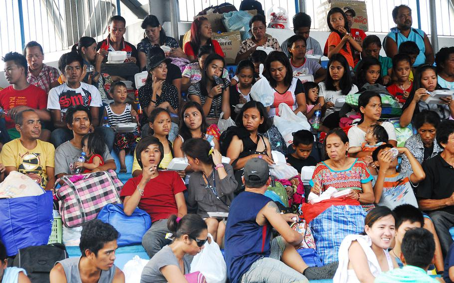 Evacuees eat Wednesday afternoon at the open-air stadium at Villamor Air Base shortly after arriving at the Manila air base from Tacloban. The U.S. military has flown thousands of evacuees to Villamor since Typhoon Haiyan.