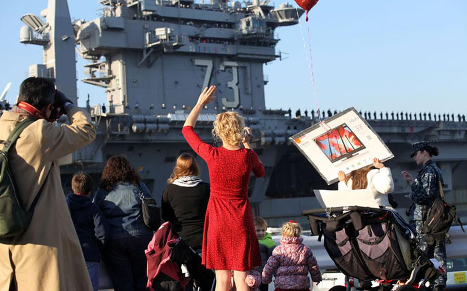 Family members wait for their loved ones to arrive as the USS George Washington returns to port at Yokosuka Naval Base Dec. 5. The carrier returned from the Phillipines where sailors provided typhoon relief and humanitarian aid.