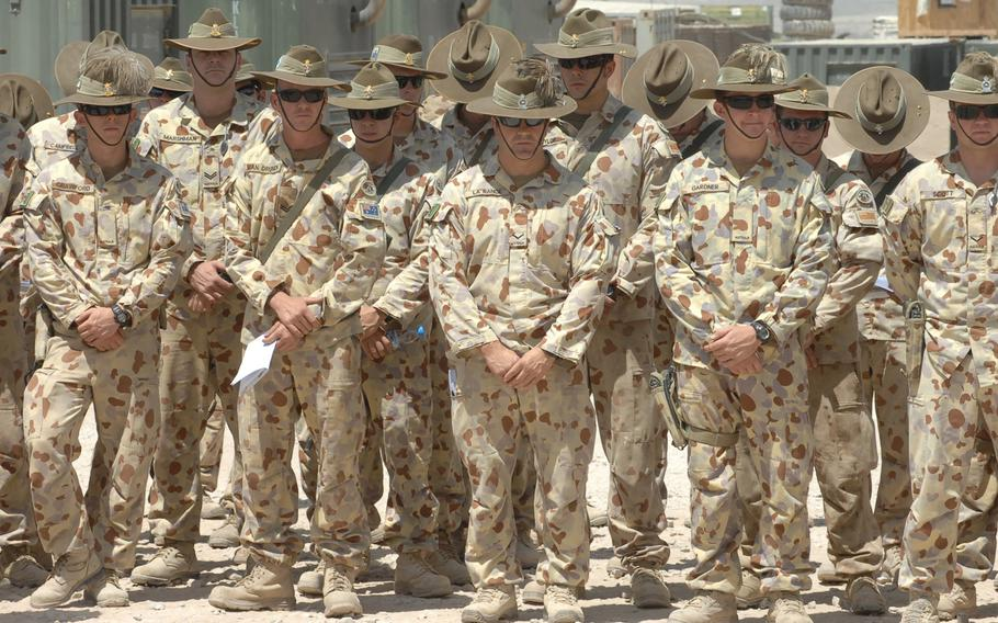 Australian soldiers participate in an August, 2010 ceremony commemorating their nation's efforts in the Vietnam war at Multinational Base Tarin Kot, Afghanistan. The Australian Defence Force has handed over control of the base to Afghan forces as part of its withdrawal from Afghanistan.