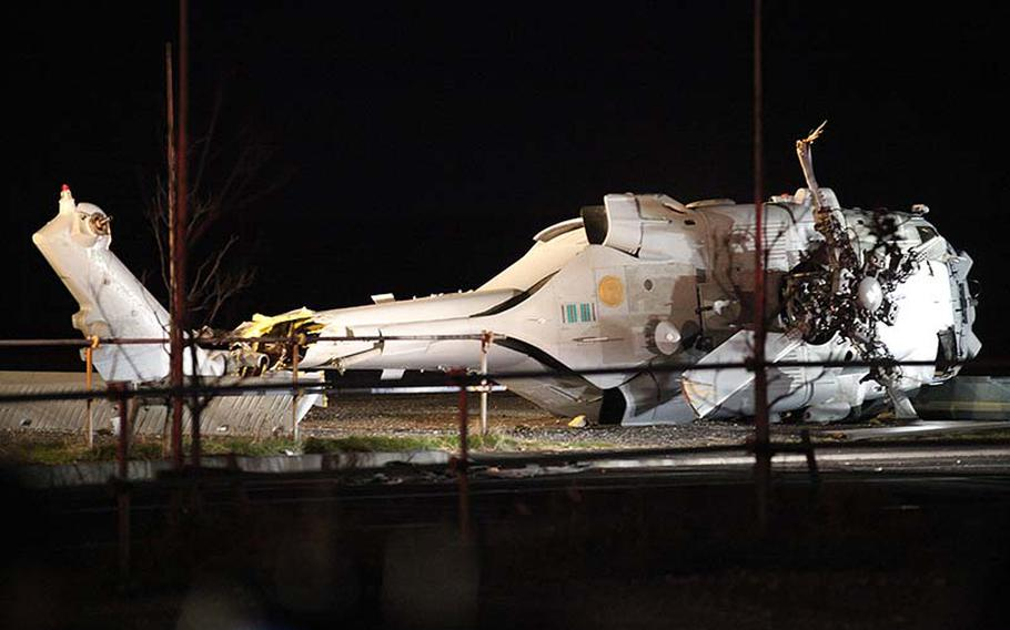The wreckage of a U.S. Navy Knighthawk helicopter sits where it crash-landed in an empty area about 10 miles southwest of Yokosuka Naval Base on Monday, Dec. 16, 2013.