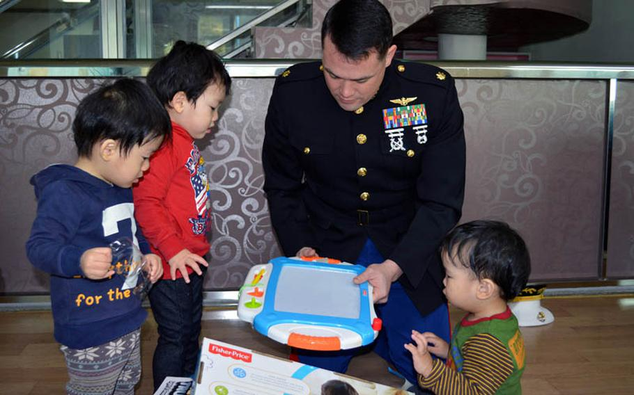 U.S. Marine Maj. Bryon deCastro unwrap a toy for orphans at Jacob's House orphanage, Pyeongtaek, South Korea, Dec. 22, 2013. DeCastro led the Toys for Tots donation drive held at Osan Air Base.