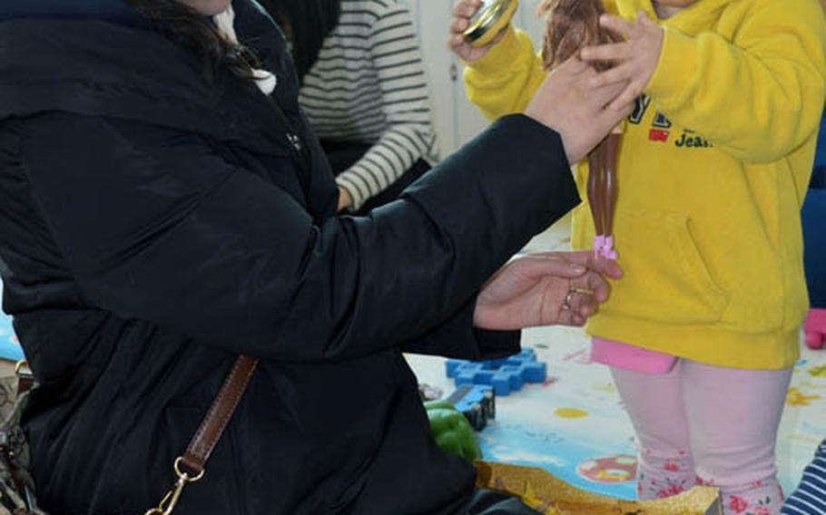 Christina JuYong Park helps presents a toy for orphan at Jacob's House orphanage, Pyeongtaek, South Korea, Dec. 22, 2013. Park is the spouse of U.S. Marine Maj. Bryon deCastro.