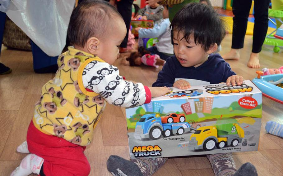 A couple of children happily receive toys at Jacob's House orphanage, Pyeongtaek, South Korea, Dec. 22, 2013. Over 300 toys were donated by U.S. military personnel stationed in South Korea.