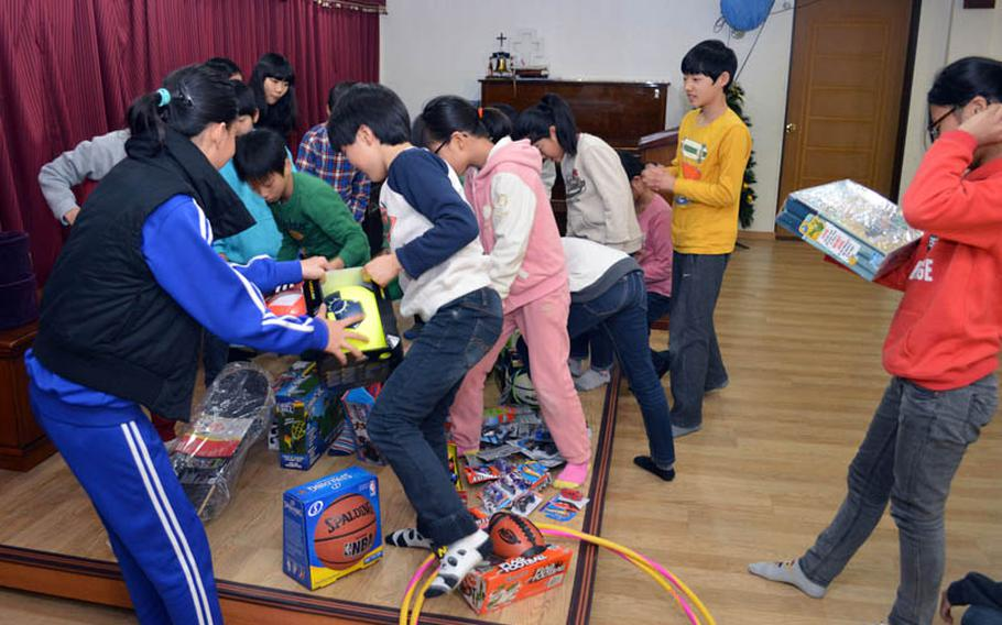 Children from Dream-Up Home orphanage select donated toys at Suwon, South Korea, on Dec. 22, 2013. U.S. Marine Maj. Bryon deCastro led the Toys for Tots donation drive held at Osan Air Base.