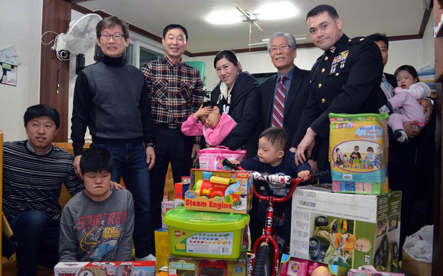 U.S. Marine Maj. Bryon deCastro, far right, Christina JuYong Park, center, and Peter Park, far left, stand with stand with the children and providers at Baby Box orphanage, Seoul, South Korea, on Dec. 22, 2013. The three helped deliver toys donated by U.S. military personnel in South Korea.