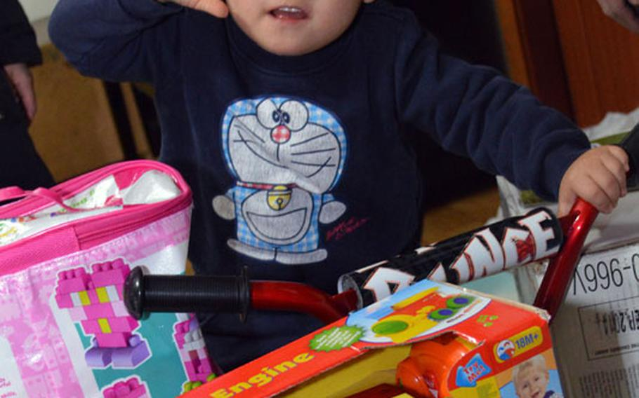 A South Korean child gives a salute to U.S. Marine Maj. Bryon deCastro, Christina JuYong Park and Peter Park for delivering toys to Baby Box orphanage at Seoul, South Korea, on Dec. 22, 2013. The three helped deliver toys donated by U.S. military personnel in South Korea.