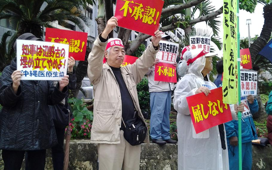 About 1,500 people rally Tuesday in front of the Okinawa prefectural government office to urge Gov. Hirokazu Nakaima to turn down a request from Tokyo to reclaim waters off Henoko in Nago to build a new runway for the Marine Corps base.