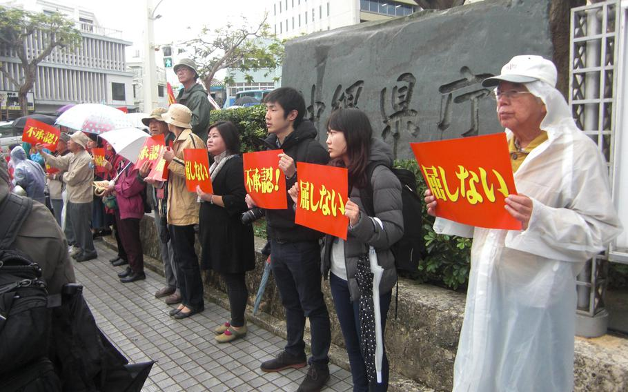 About 1,500 people Tuesday surround the Okinawa prefectural government office, urging Gov. Hirokazu Nakaima to disallow a landfill request from Tokyo to build a new Marine Corps runway off shore from Camp Schwab.