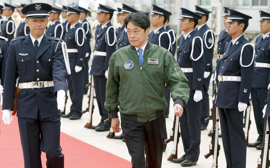 Japan's Defense Minister Itsunori Onodera, center, reviews honor guard ahead of a commemoration ceremony to mark the 60th anniversary of the foundation of Japan Air Self-Defense Force, in Irima, near Tokyo Sunday, May 25, 2014.