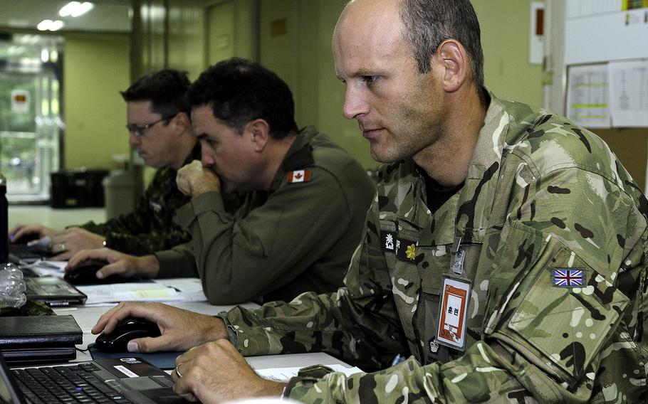Maj. Will Taylor, a British exchange officer attached to 1st Canadian Division, monitors his screen for possible enemy movement on the battlefield during Exercise Ulchi Freedom Guardian 2014 at Camp Yongin, South Korea, on Tuesday, Aug. 26, 2014.