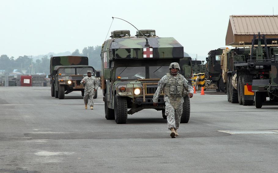 Troops and vehicles move along a staging area on Camp Humphreys, South Korea, during Exercise Ulchi Freedom Guardian 2014.