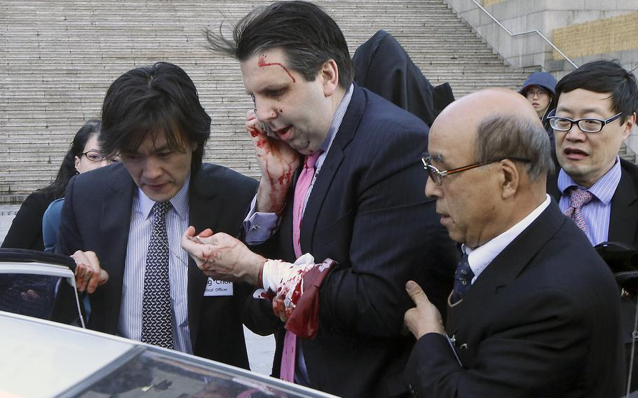 U.S. Ambassador to South Korea Mark Lippert, center, gets into a car to leave for a hospital in Seoul, South Korea, Thursday, March 5, 2015 after a man slashed Lippert on the face and wrist.